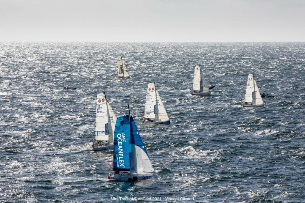 Aerial shot of five boats sailing in the ocean.