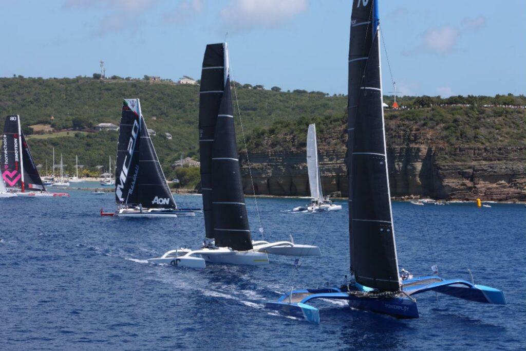 Fleet of multihulls sailing upwind on different tacks.