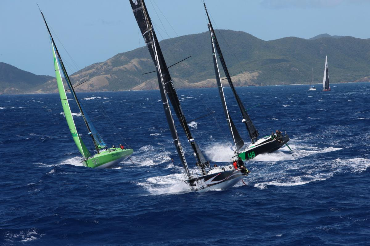 Three boats sailing upwind in choppy conditions, creating wash