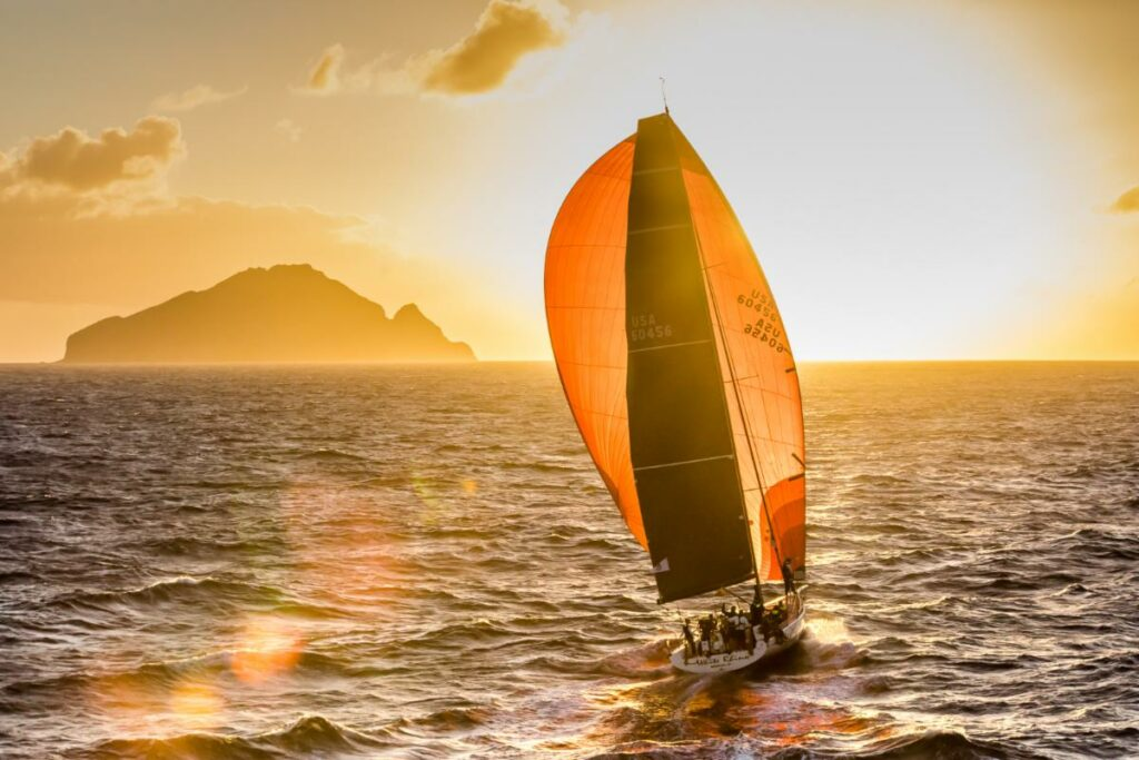 A boat sailing on a reach with a huge orange kite, into the sunset with a headland off their leeward bow.
