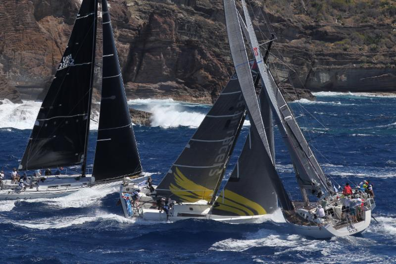 Three boats sailing upwind, with rock cliffs in background.