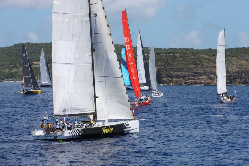 Telefonica Black sailing upwind in flat waters behind other yachts.