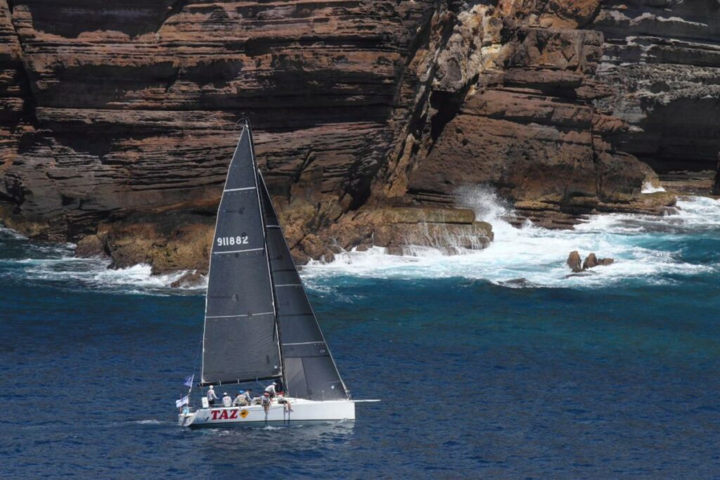 Aerial shot of Taz sailing next to rock cliff with waves breaking.