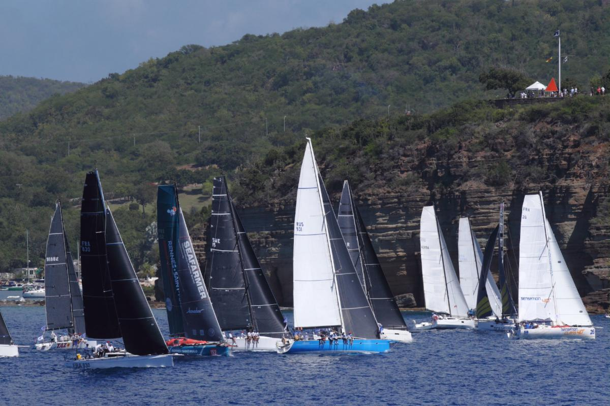 Fleet sailing upwind with cliffs in the background