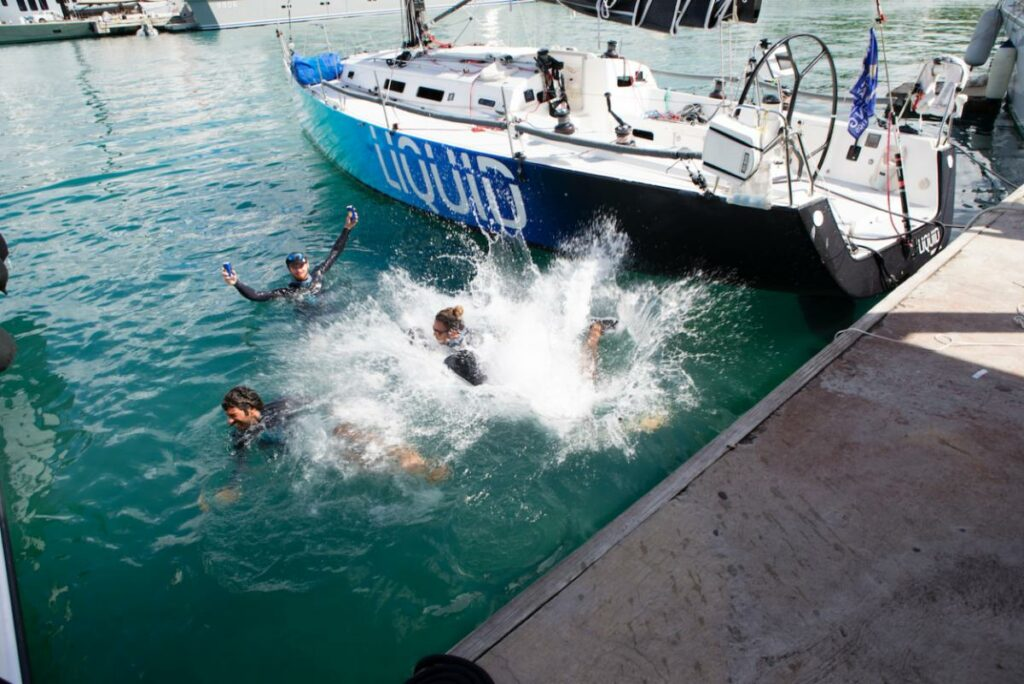 Aerial shot of the team jumping into the water off the dock, celebrating.
