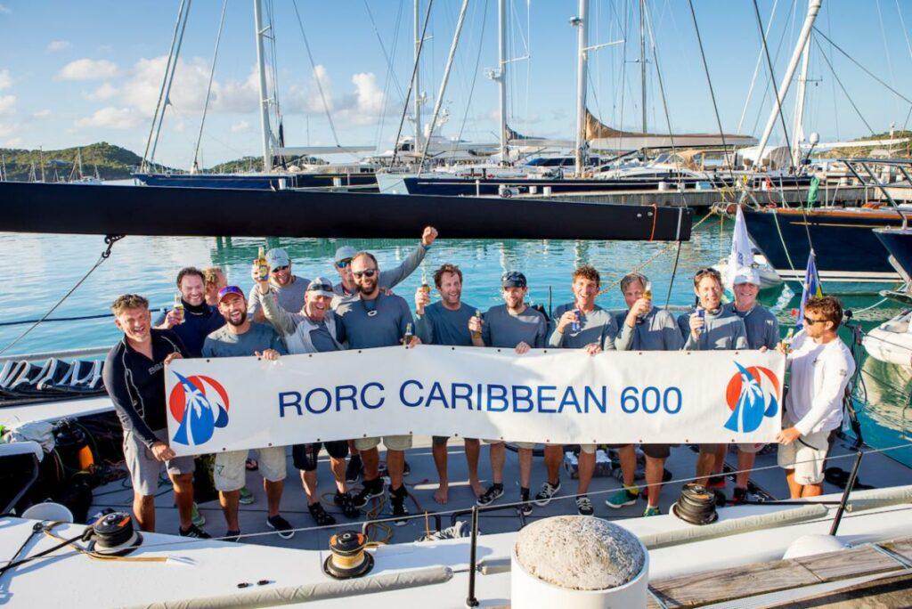 Tilmar Hansen's German TP52 Outsider  team celebrating their win on the dock holding a banner.