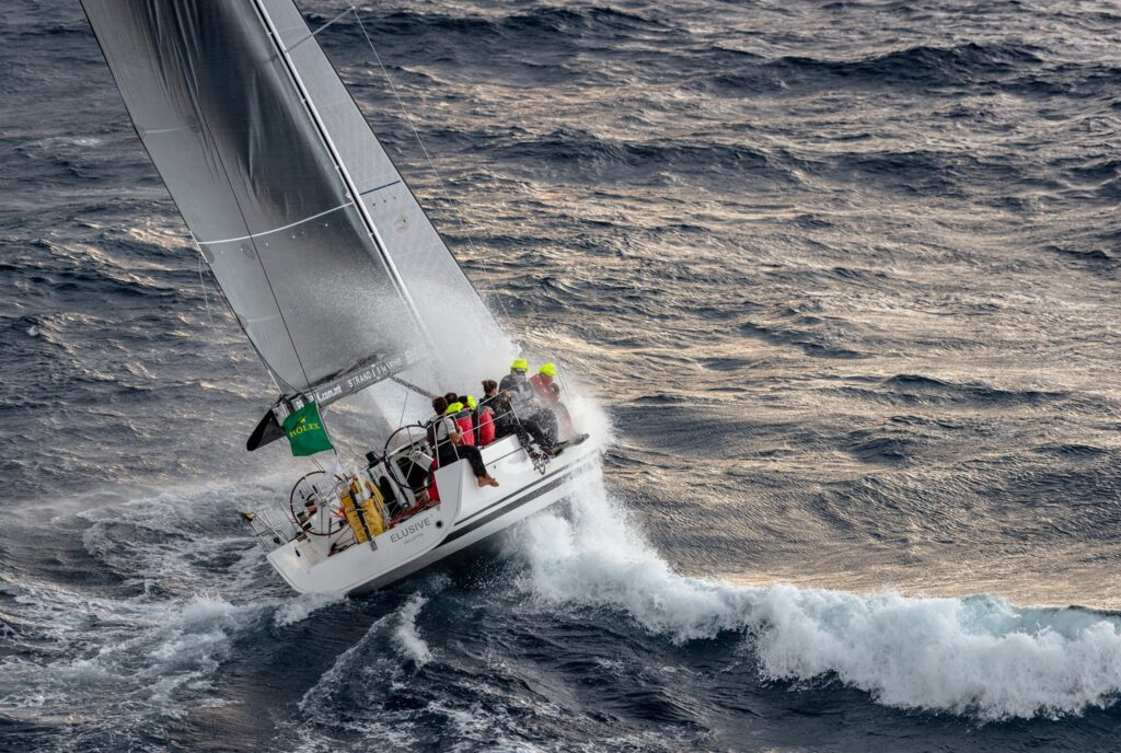 Aerial shot of Elusive 2 sailing upwind, healing, a lot of wash.