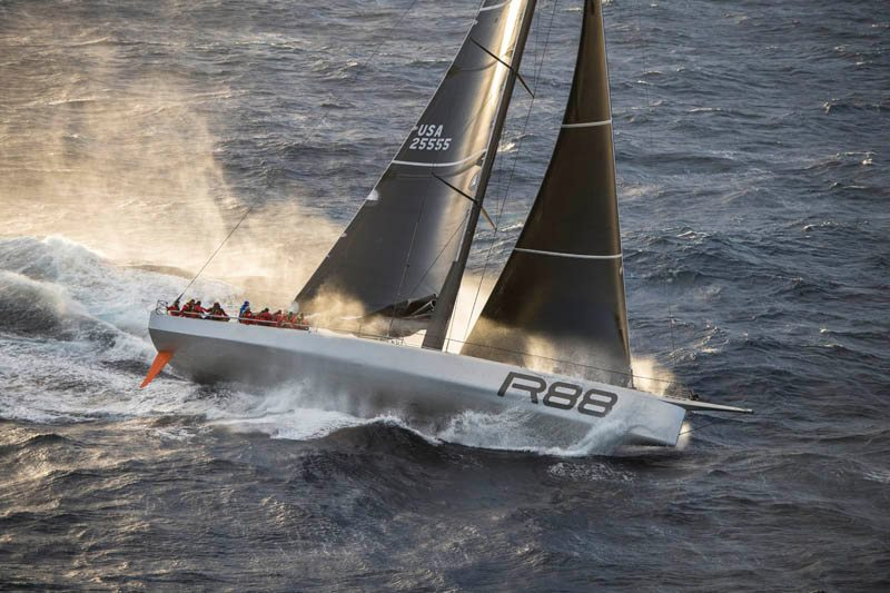 Aerial shot of Rambler sailing , leaving spray behind them.
