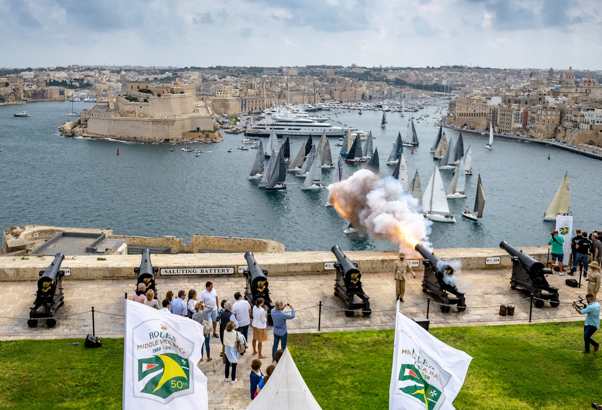 Cannons firing as the fleet start in Malta surrounded by historic looking buildings.