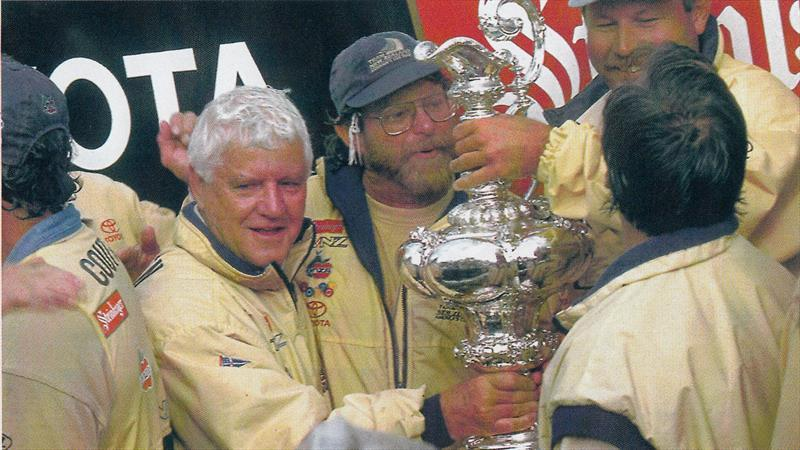 Laurie Davidson and two others smiling, holding the America's Cup.