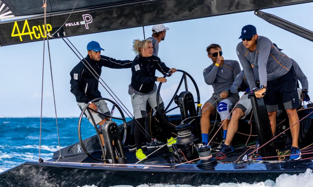 Valeriya Kovelenko at the steering wheel sailing, tactician behind her. Cre members at their stations.