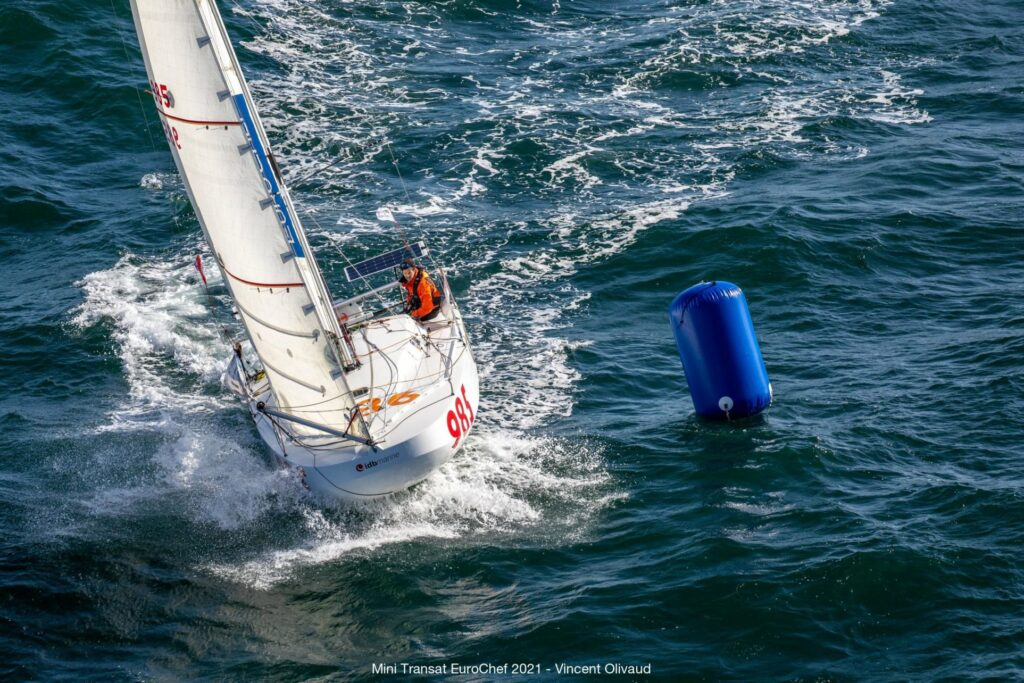 Aerial shot of Victor d'Ersu sailing, passing a blue mark.