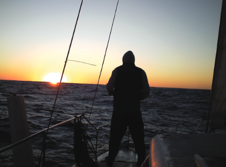 A person at the back of the sailing yacht looking onto the sunset.