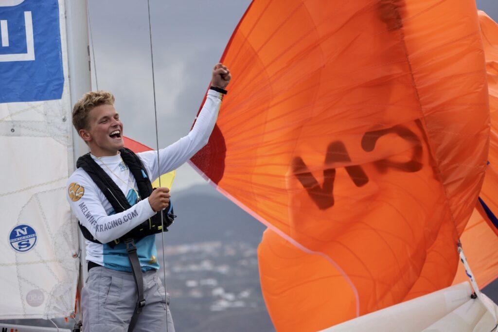 Melwin Fink holding the edge of orange sail, celebrating.