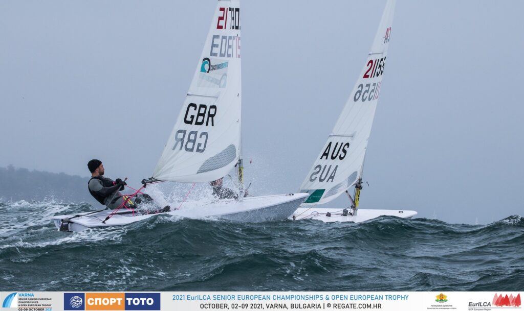 A GBR and Aussie sailor over the peak of a wave.