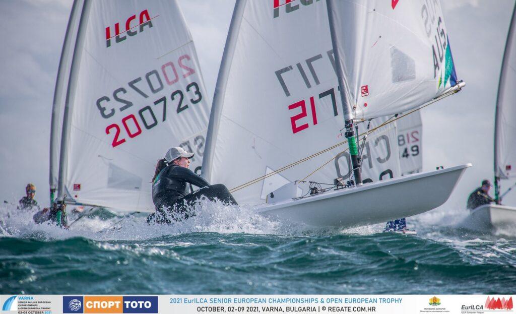 An Aussie female sailor sailing downwind, bow is up. Fleet follows.