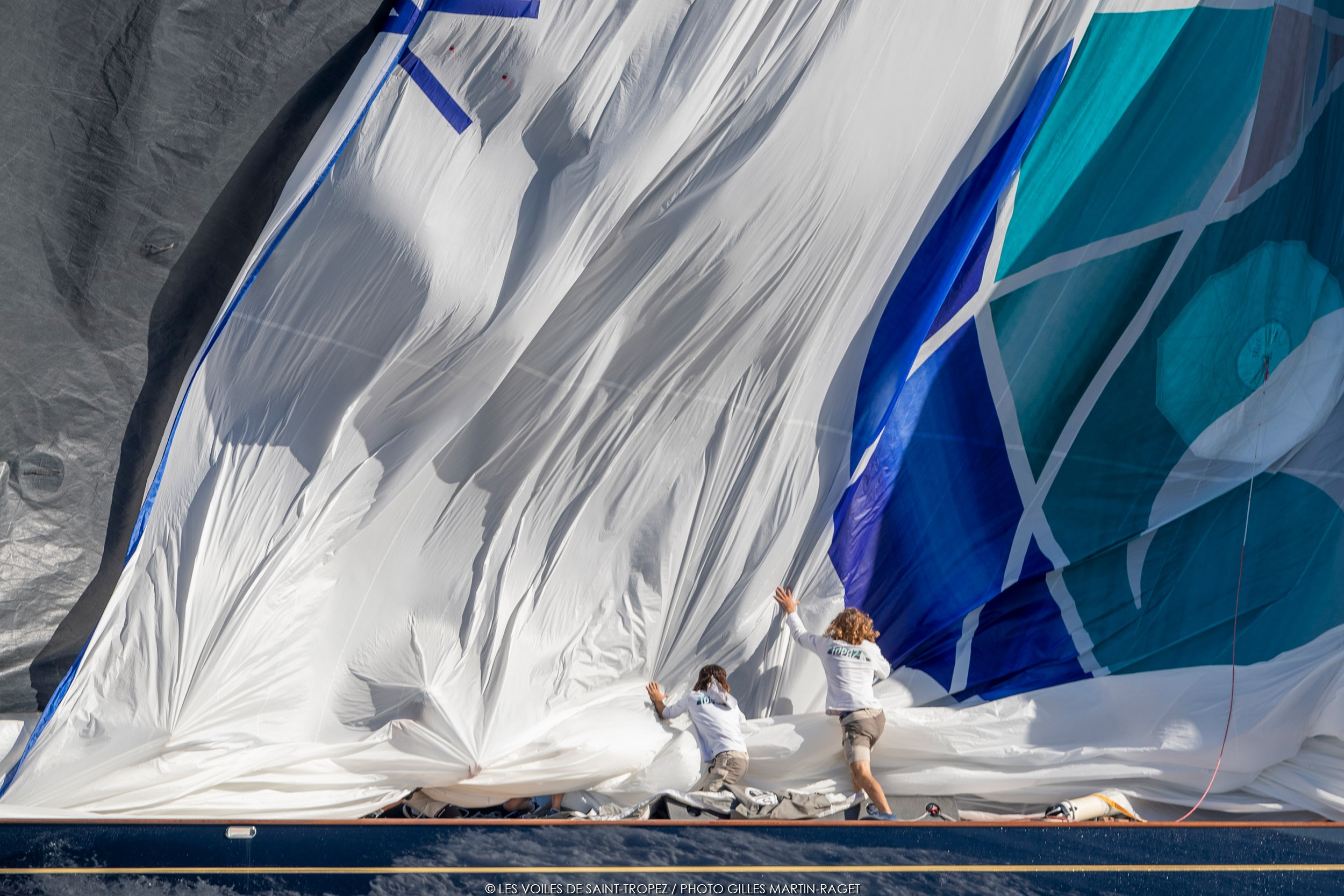 Two bow people starting to pull down the huge spinnaker on Topaz.