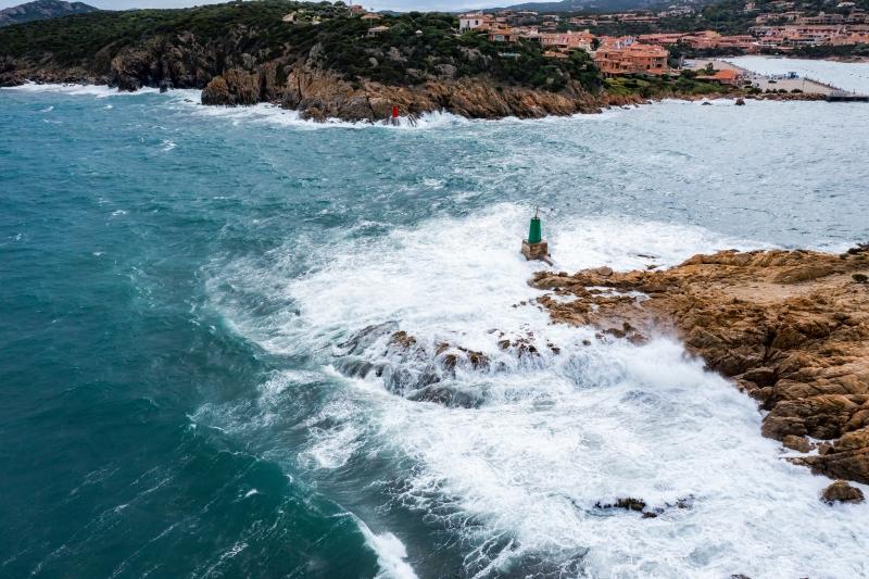Aerial shot of waves breaking onto rocks