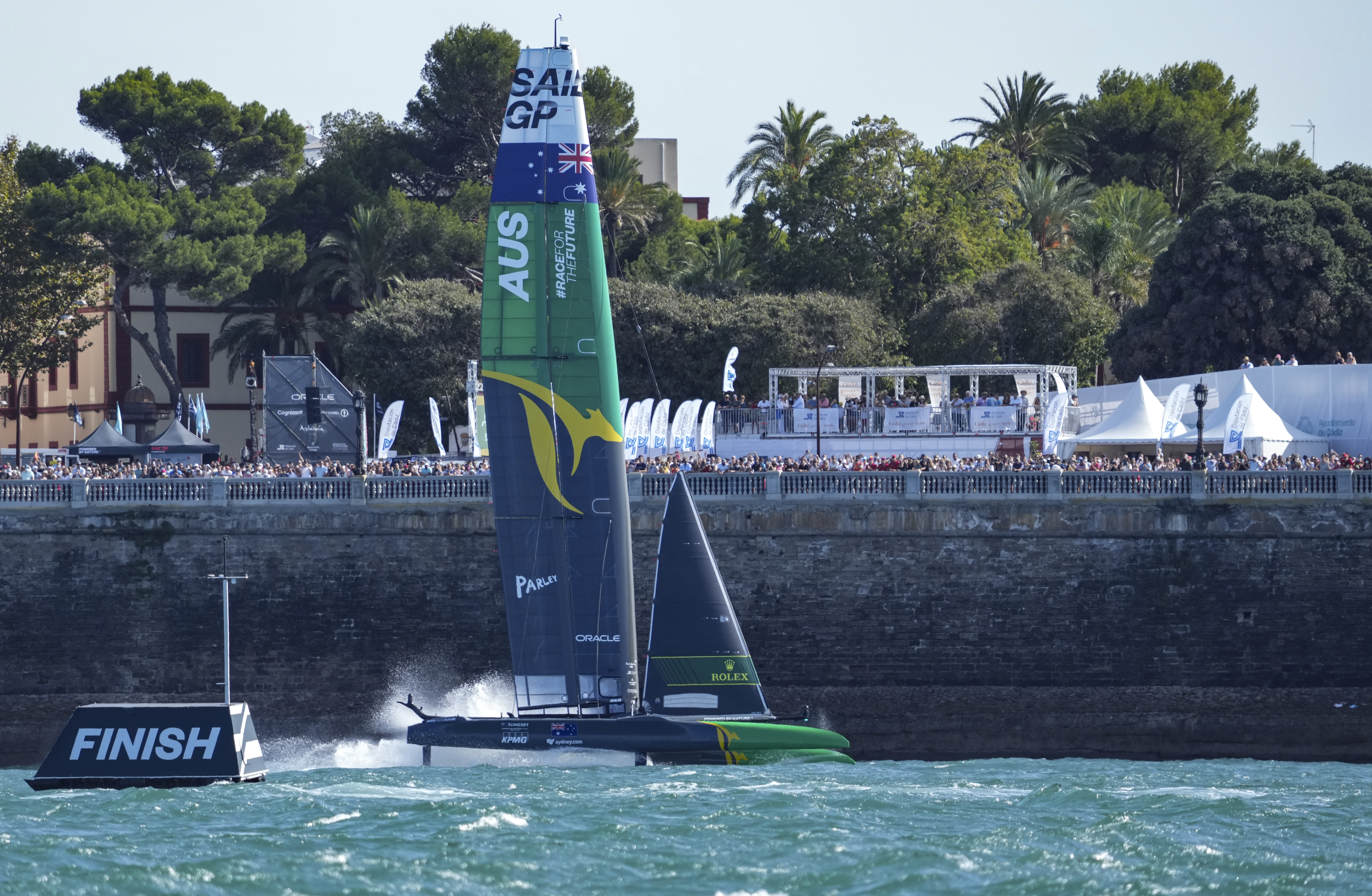 Australia sailing by a wall in choppy waters.