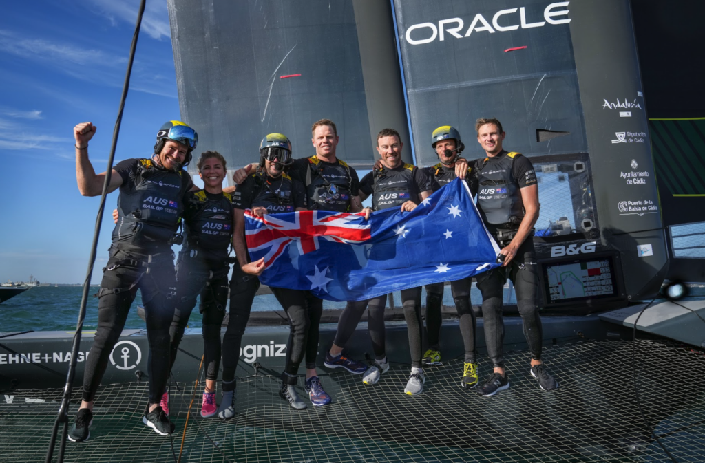 Australian SailGP Team smiling onboard the boat with the Australian flag