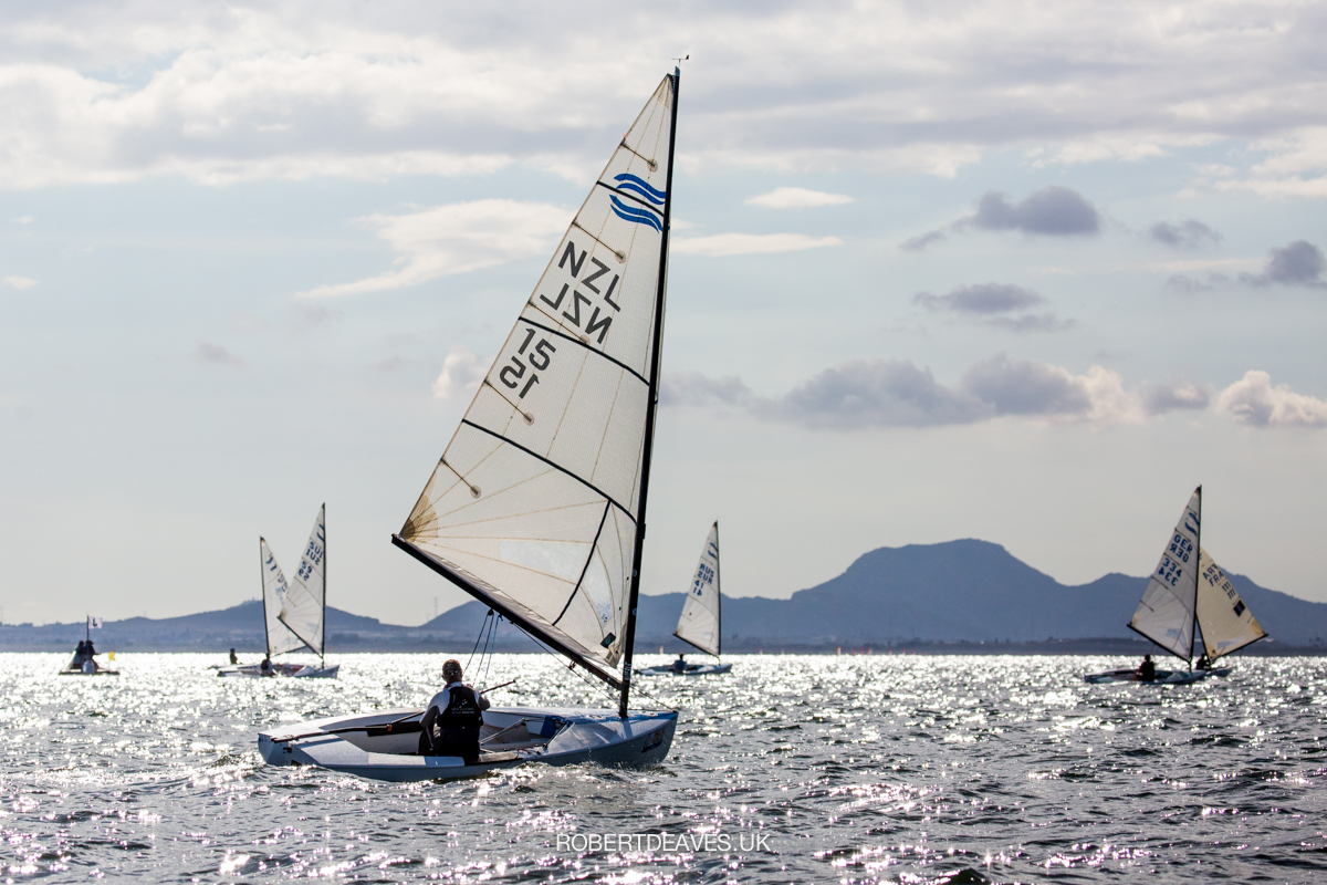 Fleet sailing downwind with mountains in the background.