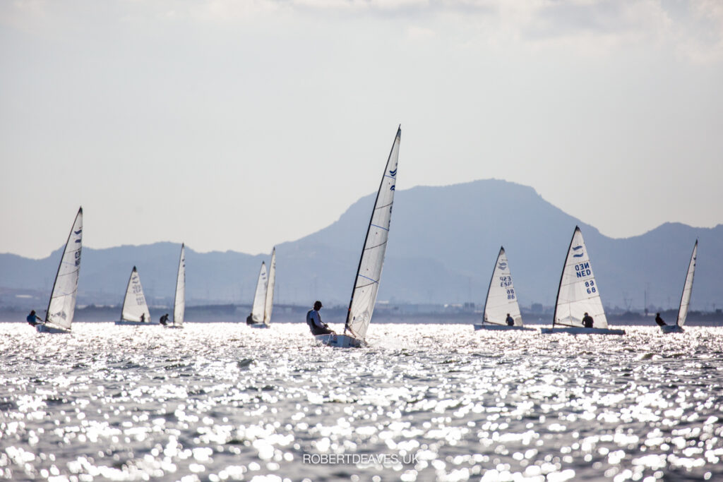Fleet sailing upwind on different tacks. Sun reflecting on the water.