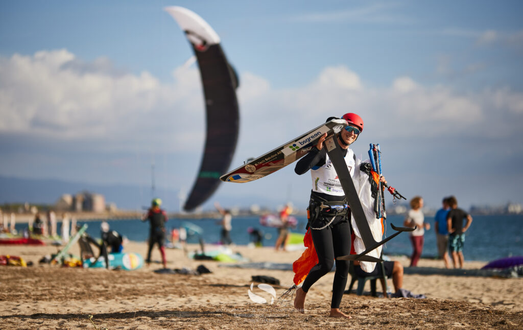 Someone holding their kite foil on the beach, smiling.