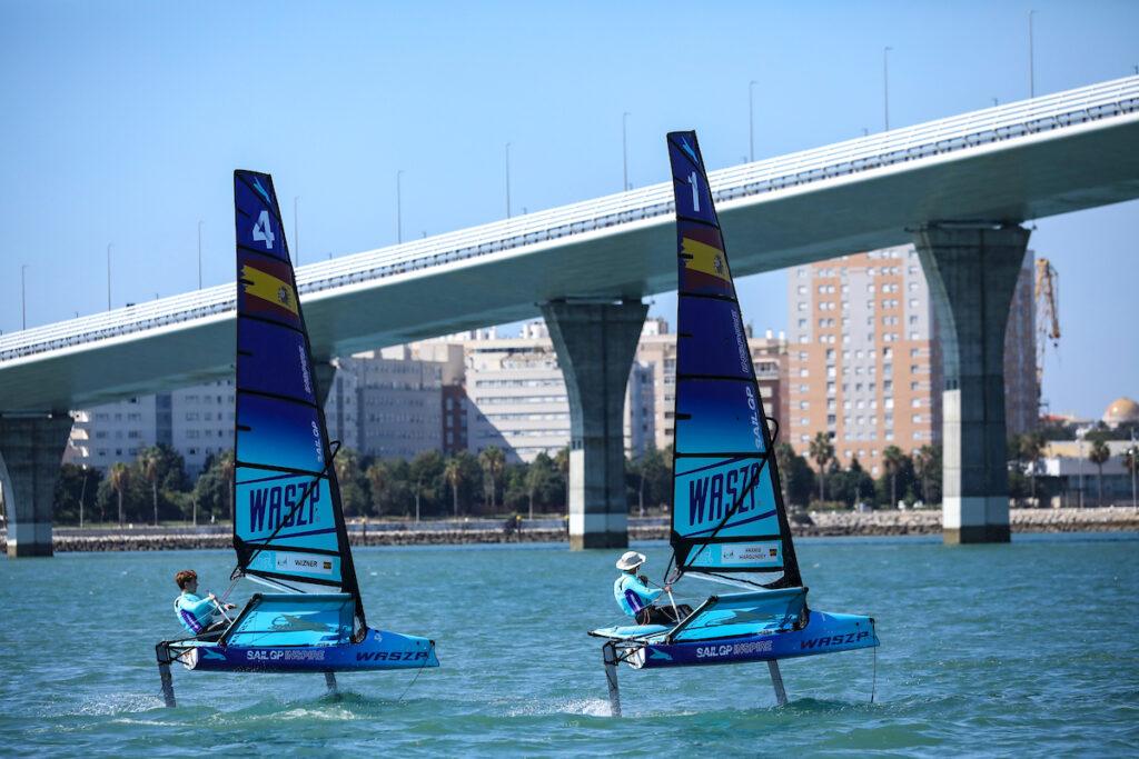Two waszps sailing upwind, heading towards a bridge.