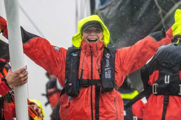 Person with wet weather jacket and life jacket on, smiling with hands in the air.