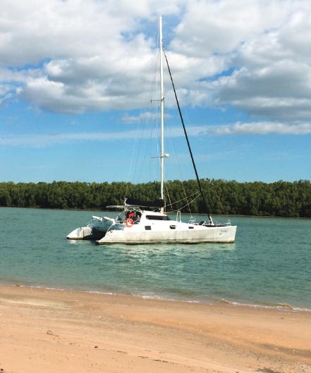 Catamaran anchored off a beach.