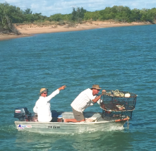 Two people on a tinny with crab pots