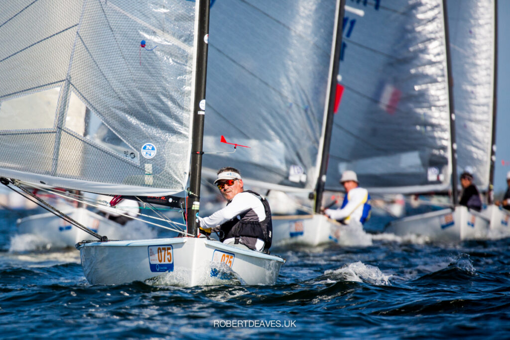 Laurent Ray sailing downwind with the fleet behind him.