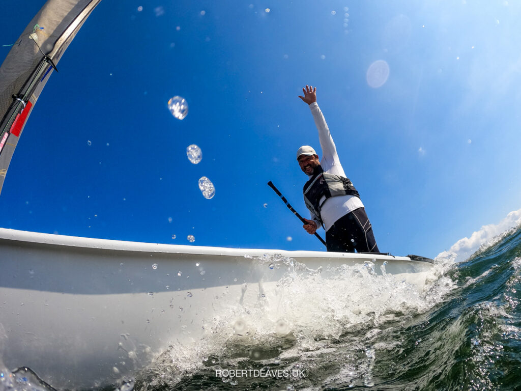Looking up from the water to Filipe Silva, smiling with his hands up.