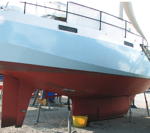Boat on dry dock with red bottom and shallow keel.