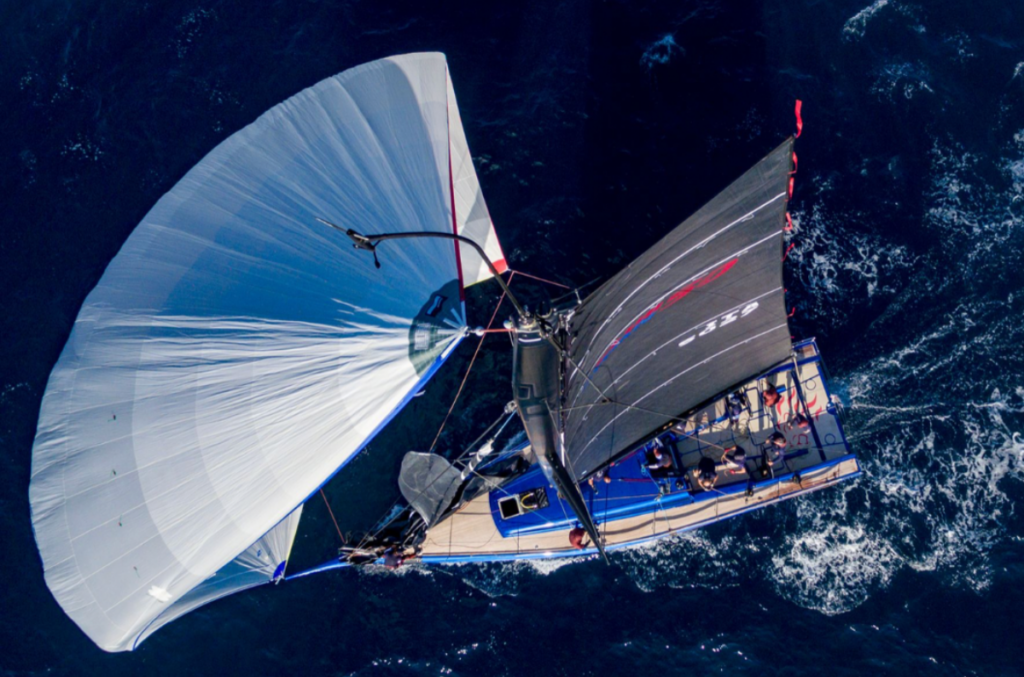 Aerial shot of a blue boat on a kite run