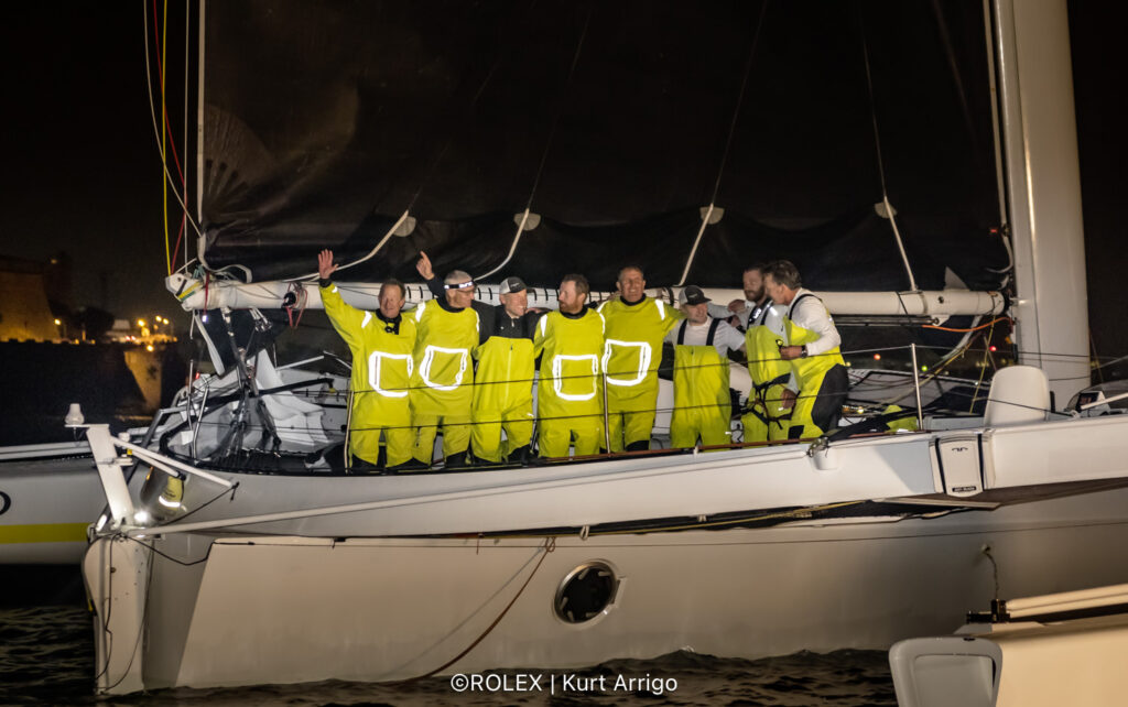 Argo crew in yellow offshore gear on the boat, smiling.