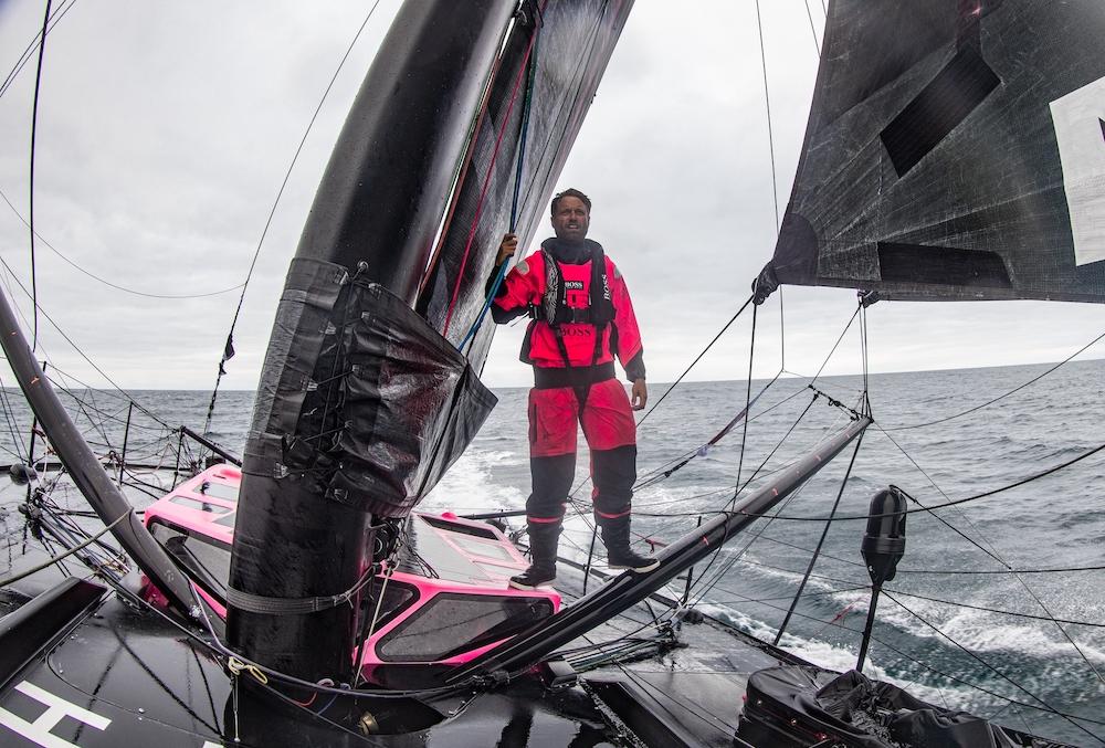 Alex Thomson standing on Hugo Boss as it sails.